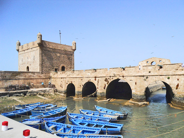 Panorámica barcas azules torre defensa puerto Essaouira